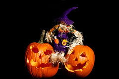 Scarecrow sitting on  Pumpkins. Halloween pumpkin with scarecrow on a black background Stock Photo