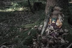 Scarecrow sitting at the root of a tree. Scarecrow with a tree branch beside it, sitting between the roots of an old tree, covered with dried leaves, in a dark royalty free stock photos