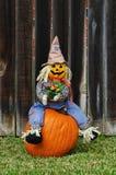 Scarecrow som sitter på pumpan Arkivfoto