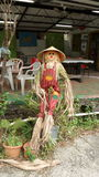 Scarecrow standing outside a cafe welcoming guests. In a farm. The scarecrow is smiling and it is tall and thin Royalty Free Stock Photo