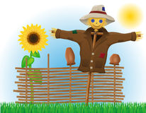 Scarecrow straw in a coat and hat with fence and sunflowers Stock Photos