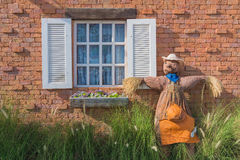 Scarecrow on the wall and windows filled with grass and flowers. Stock Photography
