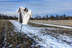 Scarecrow on winter cornfield Stock Photos