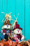 Scarecrows sitting by fall decor by teal blue wooden fence Stock Photography
