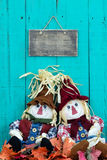 Scarecrows sitting under blank sign by fall foliage decor stock photography