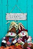 Scarecrows sitting under welcome sign with fall decor Stock Image