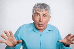 Scared созрело сморщенный мужчина выражает отрицательные эмоции, показывать и смотрит с непредвиденным выражением в камеру, носит стоковая фотография rf