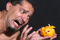Scared. Portrait of a man scared of little halloween pumpkin Royalty Free Stock Photos