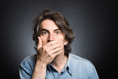 Scared adult man. With hand covering mouth and dramatic lighting stock photos