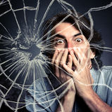 Scared adult man. With hand covering mouth and broken glass stock images