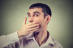 Scared adult man with hand covering his mouth Royalty Free Stock Photos