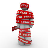 Scared Afraid Man Wrapped in Red Fear Tape. A man is wrapped in red tape reading fear representing the paralysis of being afraid and unable to move or act in the stock illustration