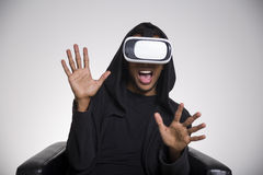 Scared African American man playing vr game. Close up of an African American guy in a black hoodie playing a virtual reality game. He is scared and grabbing his royalty free stock image