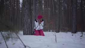 Scared African american girl calling by cell phone sitting behind tree in winter forest. Woman trying to call help. Scared African american woman calling by cell stock footage