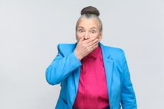 Scared aged woman closed mouth and have big eyes. Portrait of expressive grandmother with light blue suit and pink shirt standing with collected bun gray hair stock photo