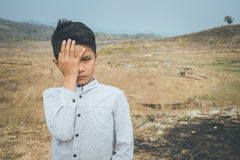 Scared and alone, young Asian child who is at high risk of being bullied, trafficked and abused, selective focus Stock Images
