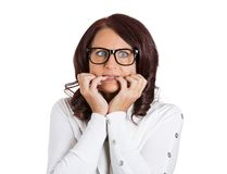 Scared anxious woman with glasses biting fingernails stock images
