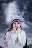 Scared Arabian person with thunderstorm Stock Image