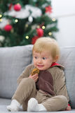 Scared baby in Christmas deer suit with cookie Royalty Free Stock Photo