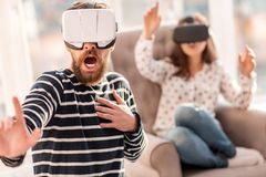 Scared bearded man protecting from VR objects. Virtual travel. Handsome emotional frightened men screaming while touching his chest and using VR headset Stock Images