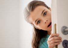 Scared beautiful girl hiding behind door at home. Childhood, fun and people concept - happy smiling beautiful girl behind door at home Royalty Free Stock Photos