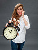 Scared beautiful woman showing stressful alarm clock for worrying deadlines Royalty Free Stock Photos
