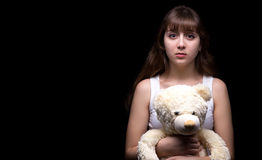 Scared blond teenage girl with teddy bear Royalty Free Stock Photography