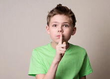 Scared boy doing a silence gesture. Kid putting finger up to lip Stock Photo