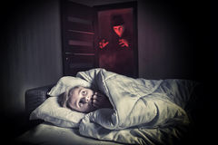 Scared boy lying in the bed while the masked stranger. Nightmare. Scared boy lying in the bed while the masked stranger standing in a doorway Royalty Free Stock Photography