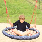 Scared boy sitting on a net swing. Scared boy sitting and swinging on a net swing made from ropes on kids playground Royalty Free Stock Photo