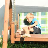 Scared boy sitting on a wooden swing Stock Images