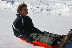 Scared Boy Sledding Down the Hill. Scared boy sledding fast down the hilll with snow background Stock Photo