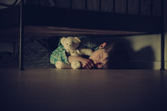 Scared Boy Sleeping Under his Bed with Teddy Bear. Scared Young Boy Sleeping Under his Bed Inside his Room While Hugging his Teddy Bear Stuffed Toy at Night Stock Photo