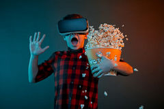 Scared boy in VR glasses spilling popcorn. Little boy in checkered shirt and VR glasses looking scared and spilling popcorn on colorful background Stock Photography