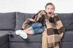 Scared boy watching tv with sister hiding under blanket Royalty Free Stock Photo