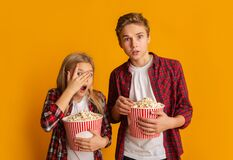 Scared brother and sister holding popcorn buckets and looking at camera
