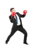 Scared business man wearing boxing gloves Stock Photo