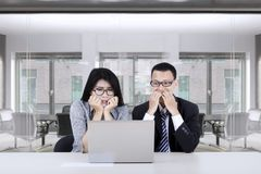 Scared business people looking at laptop Stock Photos