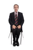 Scared businessman. Seated on a chair isolated on white Stock Photography