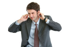 Scared businessman closing ears with fingers Stock Photo