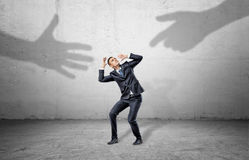 A scared businessman hides from two giant shadows of human hands reaching to him. Royalty Free Stock Image