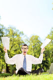 Scared businessman holding documents and screaming seated on a g Royalty Free Stock Images
