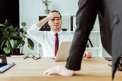 Scared businessman with laptop looking at angry boss. In office royalty free stock image