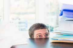Scared businessman peeking over desk Royalty Free Stock Photos