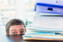 Scared businessman peeking over desk Royalty Free Stock Photography