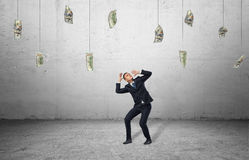 Scared businessman in protective pose with loads of money hanging in the air Stock Images