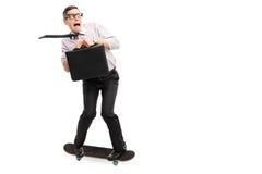Scared businessman riding a skateboard Stock Photography