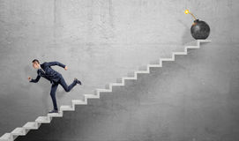 A scared businessman running down grey concrete stairs away from a large iron bomb with a lit fuse. Royalty Free Stock Photos