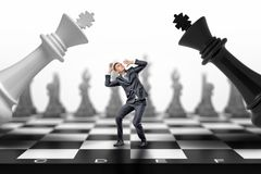 A scared businessman stands between a black and a white chess kings falling on him. royalty free stock photo