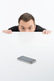Scared businessman. Terrified young man looking out of the table with mobile phone on it Royalty Free Stock Image